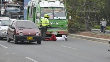 Un policía de tránsito trata de convencer al conductor que se levante de la carretera.