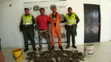 Los capturados con los cangrejos decomisados.