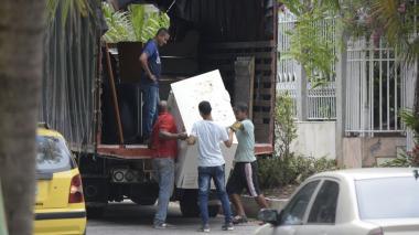 Trabajadores subiendo enseres a un camión frente a la casa de López.