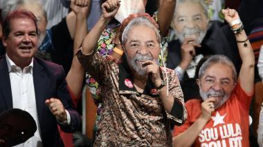 La ex presidenta brasileña Dilma Roussef (C) lleva una máscara que representa al ex presidente brasileño Luiz Inácio Lula da Silva, durante el lanzamiento de la campaña previa a la nominación de Lula antes de las elecciones presidenciales de octubre.