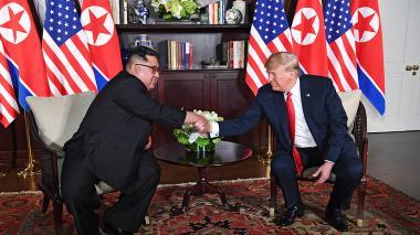 Los presidentes Kim Jong Un y Donald Trump se estrechan las manos ante la prensa de todo el mundo.