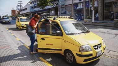 Dos mujeres dialogan con un conductor de servicio de taxi para pactar una carrera.
