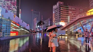 Futian, distrito de la ciudad de Shenzhen, se alumbra al caer la noche y la lluvia. Por la calle Hongli Road se respira tecnología y sitios de compras.