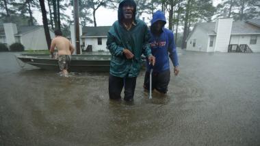 Habitantes de New Bern, Carolina del Norte, caminan entre las aguas desbordadas tras el paso de Florence.