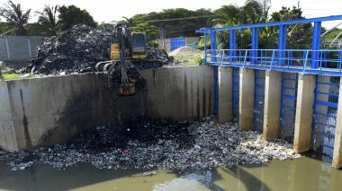 Una retroexcavadora extrae la basura del arroyo.