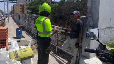 Un policía registra al albañil que preparó materiales de construcción en el andén de la carrera 51B con 92.