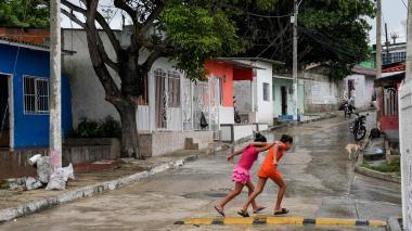 Aspecto de la calle 55C con la carrera 4A, en La Sierrita, donde dos niñas cruzan una vía inclinada.