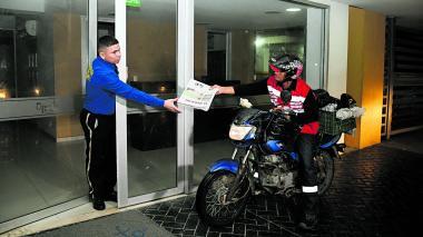 Ramón Chico  (der.) le entrega un ejemplar de EL HERALDO a un celador de un conjunto.