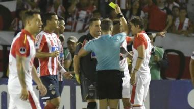 El árbitro Patricio Loustau mostrando una tarjeta amarilla.
