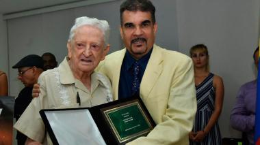 Chelo De Castro, homenajeado por su vida periodística, recibe el premio de Julio Torres, gerente de Fecolbox.
