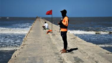 Un rescatista y un pescador, ubicados en el muelle, donde se instaló una bandera roja por los fuertes vientos.