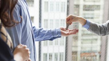 Una pareja recibiendo las llaves de su inmueble de parte de un asesor inmobiliario.