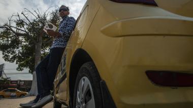 El taxista Arquímedes Correa sostiene su novela mientras posa junto a su taxi.