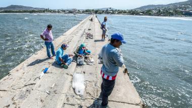 Pescadores continúan sus labores en la agrietada estructura del muelle.
