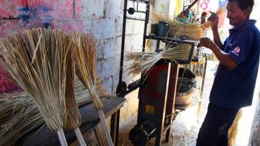 Federico Peralta corta la paja en la máquina montadora de escobas, ubicada en el patio de la casa.