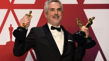 El director Alfonso Cuarón con las tres estatuillas que ganó con 'Roma'.
