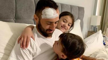 David Ospina en su casa junto a sus dos hijos.