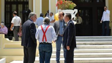 Un grupo de accionistas se reúne en los jardines de la sede Prado de Triple A, durante el receso de la junta.
