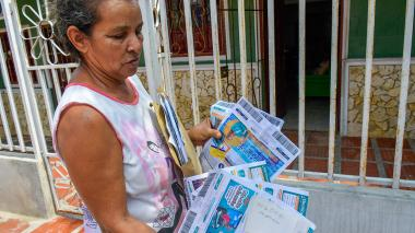Una vecina muestra sus facturas al día.