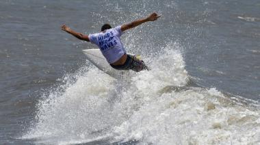 Un hombre realiza piruetas practicando surf en las playas de Pradomar.