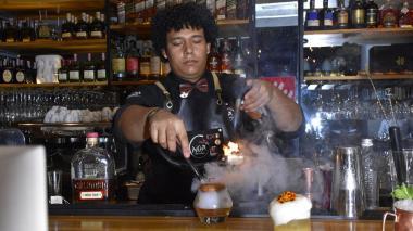 El bartender Carlitos Reyes realizando el ahumado de un coctel a base de ron.