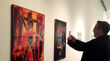 Hombre fotografía la obra de Renèe Cox, artista que se autorretrata como Raje.