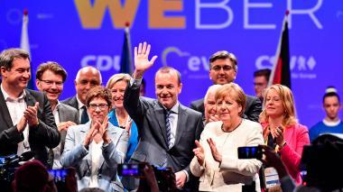El candidato del Partido Popular Europeo (PPE) a las elecciones europeas Manfred Weber (C) saluda, acompañado por la canciller alemana, Angela Merlel, durante un acto electoral en Múnich (Alemania).