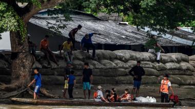 Venezolanos son transportados en canoas por el río Arauca.