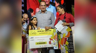 El ganador Juan L. Cediel Ibañez cuando recibía el premio junto a su hija Gaby en la tarima principal.