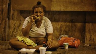 Una habitante de calle come en vía pública. Imagen de referencia.