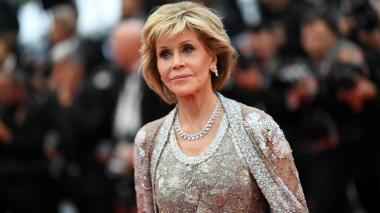 Fonda, vestida con un abrigo rojo brillante, cantó consignas de acción climática antes de ser esposada y alentada por los manifestantes.