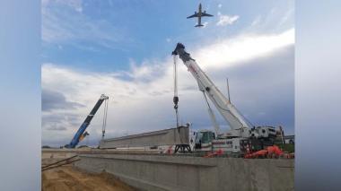 Una aeronave sobrevuela la zona donde se adelantan actualmente los trabajos de izaje de las vigas.