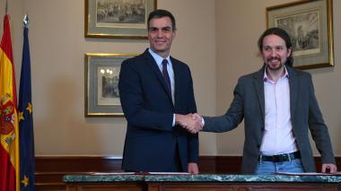 El primer ministro español titular, Pedro Sánchez (izquierda) y el líder de la alianza electoral de izquierda Unidas Podemos, Pablo Iglesias, se dan la mano después de anunciar un acuerdo para formar un gobierno, dos días después de una elección general repetida.