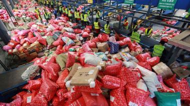 Trabajadores organizan paquetes en un centro de distribución de Alibaba.