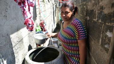 Mery Sánchez  muestra los tanques en los que almacena el agua con que lava la ropa y las cosas de su hogar.