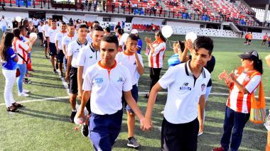 Jugadores de Junior y Colombia Sports agarrados de manos en la cancha.