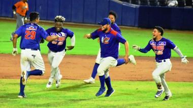 Los peloteros de Caimanes corren a felicitar a Álvaro Noriega tras la jugada que significó la victoria de Caimanes.