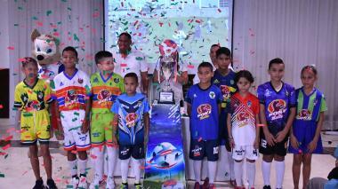 Niños y niñas rodean la Copa Caribe en la presentación de la competencia.