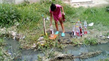 Una niña envasa agua en botellas de plástico a pesar de las recomendaciones.