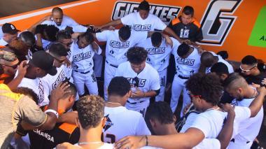 Peloteros de la novena Gigantes de Barranquilla reunidos orando antes de un juego de la final.