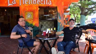 Jesús López y Humberto Haag conversan bajo la sombra de un árbol en un establecimiento en Boston.