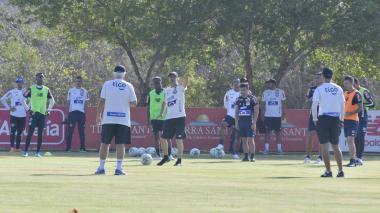 El preparador físico del Junior, Alejandro Cáceres, da indicaciones ante los jugadores y Comesaña.