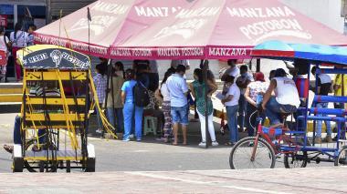 Personas hacen fila para entrar a un supermercado.