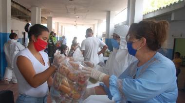La secretaria de Educación entrega una bolsa de alimentos a una madre de familia.