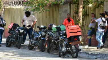 Varios trabajadores del servicio de domicilio en motocicleta están en una calle de Barranquilla.