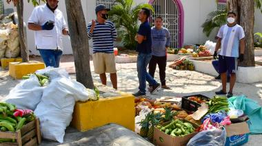 Varios de los vendedores con las frutas y verduras en el suelo, tras el decomiso de sus carretillas.