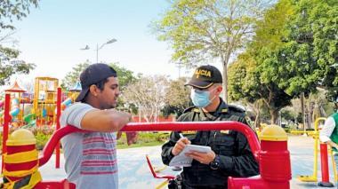Un miembro de la Policía le impone un comparendo a un ciudadano por incumplir la medida de aislamiento social y de protección (sin tapaboca).