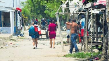 Un grupo de personas caminan por una calle del barrio Mesolandia en el municipio de Malambo.