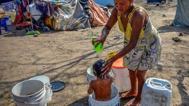 Mujer indígena yukpa baña a su pequeño hijo debajo del puente de la Murillo en Barranquilla.