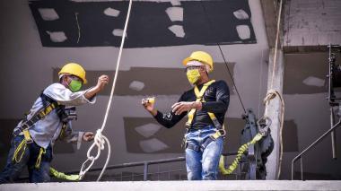 Dos obreros realizan trabajos en una obra de construcción de vivienda.